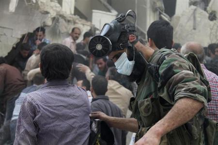A man, with a chemical mask on his head, searches for survivors from the rubble of a damaged area, what activists said was a result of an airstrike by the Syrian Regime, in Al-Sukkari neighborhood in Aleppo April 7, 2013. REUTERS/Haleem Al-Halabi