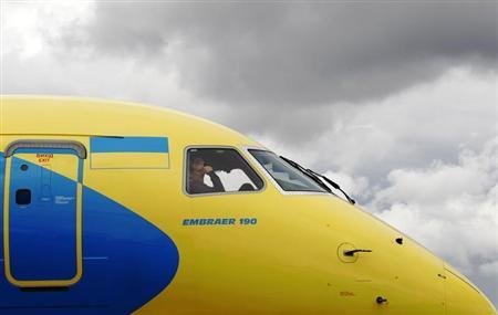 A crew member sits in the cockpit as an Embraer 190 is guided onto its stand ahead of the Farnborough Airshow 2012 in southern England July 7, 2012. REUTERS/Luke MacGregor