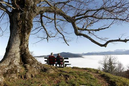 An elderly couple sits on a bench on the peak of Mount Hochwacht (988 metres/3241 ft) as high fog covers the landscape around the Swiss town of Zug November 20, 2012. Reuters/Arnd Wiegmann