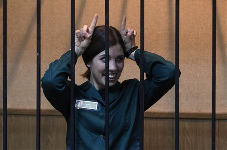 Pussy Riot band member Nadia Tolokonnikova gestures as she looks out from a holding cell during a court hearing in the town of Zubova Polyana April 26, 2013. REUTERS/Mikhail Voskresensky