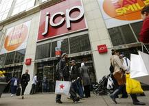 A man with a Macy's bag walks past the J.C. Penney's store in New York, April 11, 2013. REUTERS/Brendan McDermid