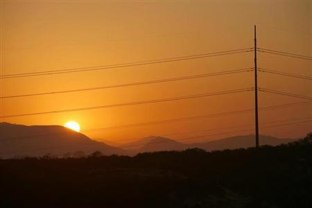 The sun rises over electric power lines in Encinitas, California September 4, 2007. REUTERS/Mike Blake/Files