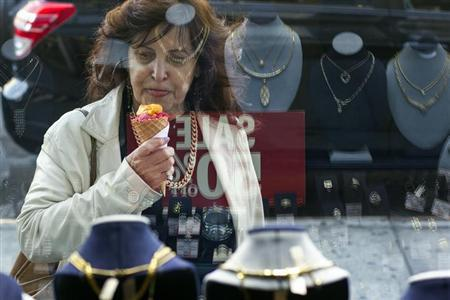 A woman eats ice cream as she looks at the display in the window of a Gold Standard jewellery store that specializes in purchasing raw gold and silver in New York April 15, 2013. REUTERS/Lucas Jackson