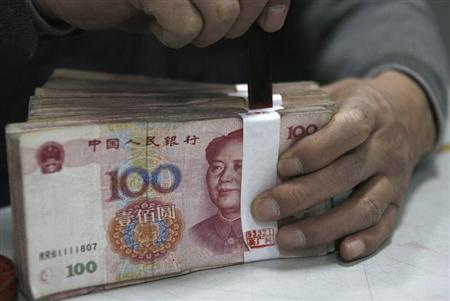 An employee seals a stack of yuan banknotes at a branch of Industrial and Commercial Bank of China in Huaibei, Anhui province April 6, 2011. REUTERS/Stringer