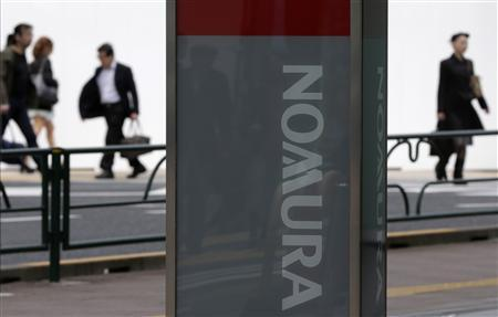 People walk behind a signboard of Nomura Securities outside its branch in Tokyo April 25, 2013. REUTERS/Toru Hanai