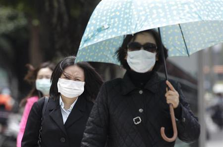 Pedestrians wearing medical masks walk on the street outside National Taiwan University Hospital in Taipei April 26, 2013. REUTERS/Pichi Chuang