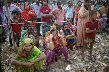 Locals gather as they watch a rescue operation of the collapsed Rana Plaza building, in Savar, 30 km (19 miles) outside Dhaka April 26, 2013. REUTERS/Andrew Biraj