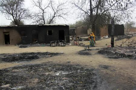 A woman carrying a child stands near burnt houses in the aftermath of what Nigerian authorities said was heavy fighting between security forces and Islamist militants in Baga, a fishing town on the shores of Lake Chad, adjacent to the Chadian border, April 21, 2013. REUTERS/Stringer