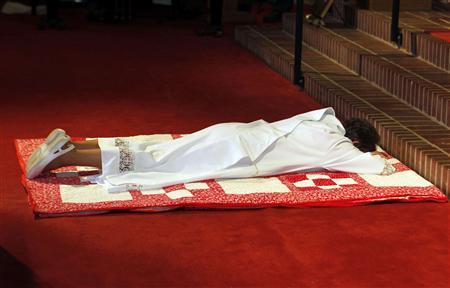Rosemarie Smead, a 70-year-old Kentucky woman, lies prostrate on the floor as the audience prays for the blessing of the Saints, before being ordained a Roman Catholic priest during a Celebration of Ordination at St. Andrew's United Church of Christ in Louisville, Kentucky April 27, 2013. Smead was ordained as part of a dissident group operating outside official Roman Catholic Church authority. REUTERS-John Sommers II