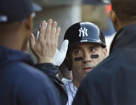 New York Yankees designated hitter Travis Hafner celebrates with teammates in the dugout after he hit a three-run home run against the Toronto Blue Jays in the fourth inning of their MLB American League game at Yankee Stadium in New York, April 27, 2013. REUTERS/Ray Stubblebine