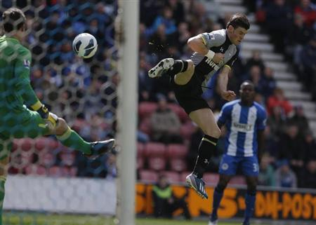 Tottenham Hotspur's Gareth Bale (R) charges down a clearance from Wigan Athletic's goalkeeper Joel Robles (L) to score during their English Premier League soccer match at the DW Stadium in Wigan, northern England, April 27, 2013. REUTERS/Phil Noble