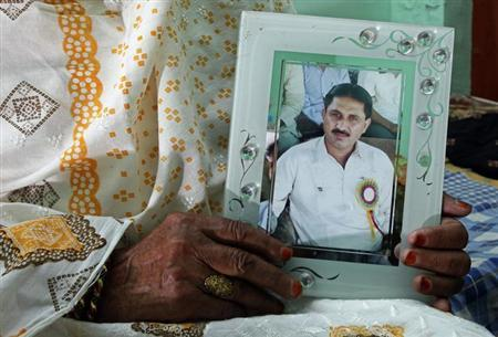 Ghulam Sakina, 85, mother of Jamshed Dasti, a former member of parliament and election rival of Hina Rabbani Khar, Pakistan's former foreign minister, shows her son's portrait during an interview with Reuters in Muzaffargarh in Punjab province April 9, 2013. REUTERS/Mohsin Raza