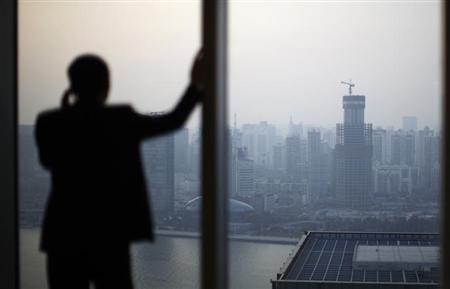 A man talks on the phone as he looks at the skyline of Shanghai March 28, 2012. REUTERS/Carlos Barria/Files