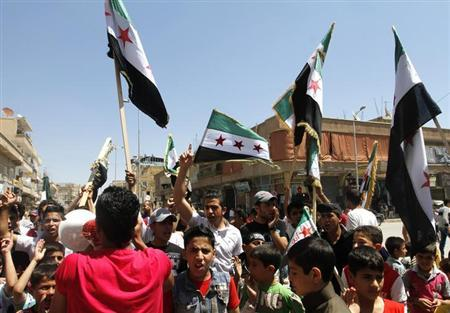 Demonstrators chant slogans and wave Syrian opposition flags as a boy shouts into a loud hailer during a protest against President Bashar al-Assad afer Friday prayers in Raqqa province, east Syria April 26, 2013. REUTERS/Nour Kelze
