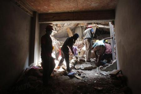 Rescue workers attempt to rescue garment workers from the rubble of the collapsed Rana Plaza building, in Savar, 30 km (19 miles) outside Dhaka April 28, 2013. REUTERS/Andrew Biraj