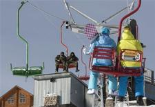 Skiers sit in a chair-lift while ascending to the top of Elbrus's neighbouring Mount Cheget, with security personnel seen in the background, February 3, 2013. REUTERS/Kazbek Basayev