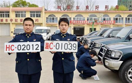 Officers of China's navy pose for photographs with the new (L) and old military car licence plates, in Qinhuangdao, Hebei province April 28, 2013. REUTERS/Stringer