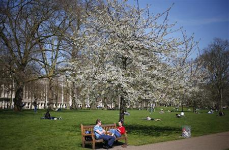 A couple sit under a tree on a warm spring day in St James's Park in central London April 23, 2013. REUTERS/Andrew Winning