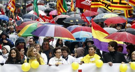 People hold umbrellas as they march with a banner during a protest against government austerity measures in Barcelona April 28, 2013. REUTERS/Albert Gea