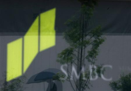 A pedestrian under an umbrella is reflected on a sign of the Sumitomo Mitsui Banking Corporation outside its branch in Tokyo May 15, 2012. REUTERS/Yuriko Nakao
