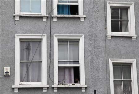 A woman sits at a window in London April 22, 2013. REUTERS/Stefan Wermuth