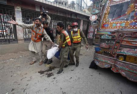 Rescue workers carry a dead body away from the site of a blast at University Road in Peshawar April 29, 2013. REUTERS/Fayaz Aziz