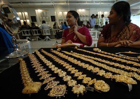 A customer looks in a mirror after wearing a gold earring inside a jewellery shop in Hyderabad September 8, 2009. REUTERS/Krishnendu Halder/Files