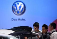Guests look at a Volkswagen car during the media day at 15th Shanghai International Automobile Industry Exhibition in Shanghai April 20, 2013. REUTERS/Aly Song