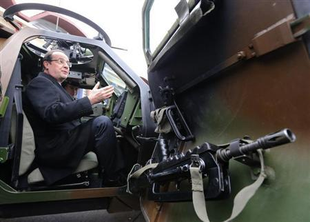 French President Francois Hollande sits in an armoured military vehicle as he visits the troops of 12th cuirassiers regiment at the military base of Olivet, central France, as part of his New Year's greetings to the French army forces, January 9, 2013. REUTERS/Jacques Brinon/Pool