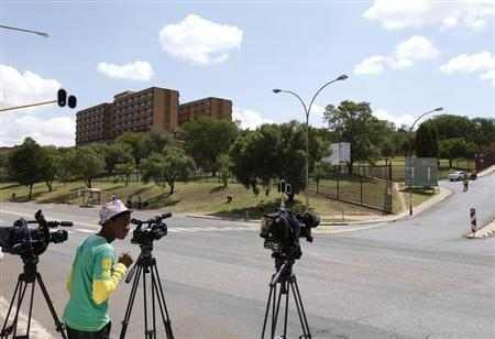 Members of the media are seen outside the One Military Hospital, which former South African President Nelson Mandela was previously admitted into, in Pretoria March 28, 2013. REUTERS/Siphiwe Sibeko