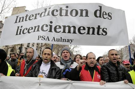 Employees of PSA Peugeot Citroen hold a banner during a demonstration in Paris March 18, 2013 to protest against the closure of the PSA Aulnay automobile plant and the government's economic policy and industrial layoffs. REUTERS/Jacky Naegelen