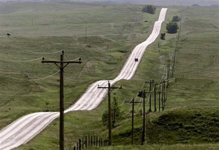 A lone vehicle travels one of the many monotonous roads on the Pine Ridge Indian Reservation in South Dakota. REUTERS/ANDY CLARK