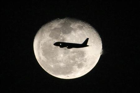 A passenger jet flies in front of the moon in Bogota November 1,2012. REUTERS/Felipe Caicedo