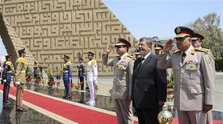 Egypt's President Mohamed Mursi (2nd R) stands after laying a wreath during his visit to the tomb of former President Anwar al-Sadat and the Tomb of the Unknown Soldier during the commemoration of Sinai Liberation Day in Cairo April 24, 2013. REUTERS/Egyptian Presidency/Handout