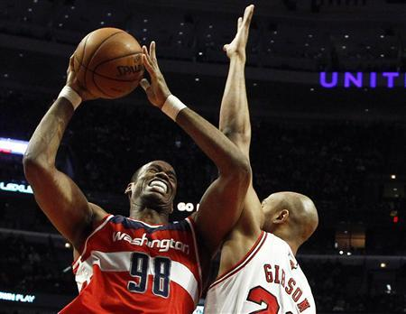 Washington Wizards' Jason Collins (L) goes to the basket against Chicago Bulls' Taj Gibson during the first half of their NBA basketball game in Chicago, Illinois, in this April 17, 2013 file photo. REUTERS/Jim Young/Files