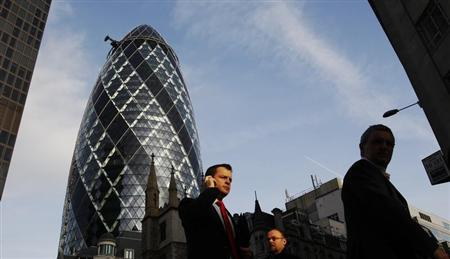 Pedestrians walk past the 'Gherkin' building in the City of London January 21, 2010. REUTERS/Luke MacGregor