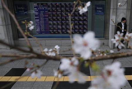 A man stands next to an electronic stock quotation board as cherry blossoms are in full bloom outside a brokerage in Tokyo March 25, 2013. REUTERS/Issei Kato