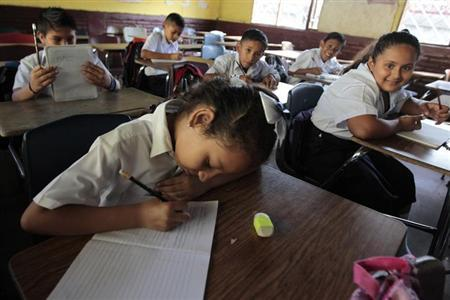 A student writes down in her note book on the first day of school in Managua February 11, 2013. REUTERS/Oswaldo Rivas/Files