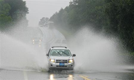 An SUV plows through water that covers a section of Highway 90 leading into Live Oak, Florida, June 26, 2012. REUTERS/Phil Sears