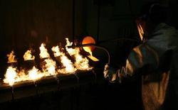 Работник завода в Красноярске отливает слиток золота, 25 февраля 2013 года. Темпы роста российской промышленности в апреле оказались одними из самых низких за последние полтора года с замедлением динамики новых заказов, показал индекс менеджеров по снабжению (PMI). REUTERS/Ilya Naymushin