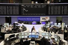 Traders work at their desks in front of the DAX board at the Frankfurt stock exchange April 30, 2013. REUTERS/Remote/Marte Kiessling