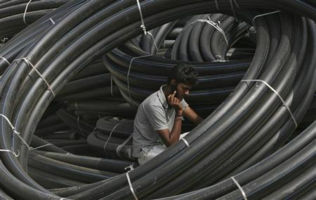 A construction supervisor speaks on a mobile phone amid rolls of underground telephone cable pipes on the outskirts of the southern Indian city of Hyderabad November 29, 2010. REUTERS/Krishnendu Halder