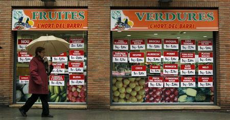 A woman walks past price-boards in a greengrocer in Barcelona, April 29, 2013. REUTERS/Albert Gea