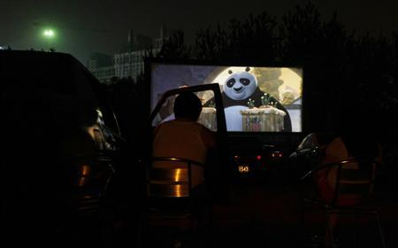 A couple watch the animated film ''Kung Fu Panda 2'' next to their car at a drive-in cinema in Beijing in this June 6, 2011 file photo. REUTERS/Jason Lee/Files
