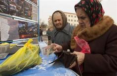 Женщина расплачивается на уличном рынке в Минске 31 марта 2013 года. Обремененная $12-миллиардным внешним долгом Белоруссия получила очередной транш на $440 миллионов из кредита контролируемого Россией Антикризисного фонда ЕврАзЭС, несмотря на отказ выполнять условия о приватизации госсобственности. REUTERS/Vasily Fedosenko