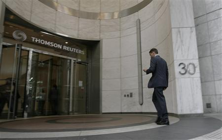 A worker enters the Thomson Reuters building in the Canary Wharf financial district of London in this August 6, 2009 file photo. REUTERS/Simon Newman/Files