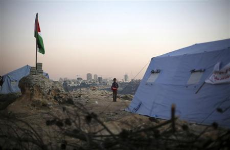 A boy stands near a Palestinian flag placed near newly-erected tents in the West Bank village of Beit Iksa, between Ramallah and Jerusalem January 20, 2013. REUTERS/Mohamad Torokman