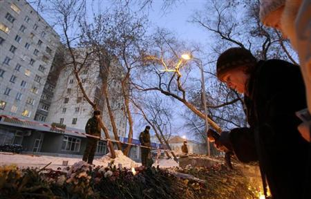 A woman lights a candle in front of the Lame Horse nightclub in the centre of Perm, 1,150 km (720 miles) east of Moscow, December 6, 2009. REUTERS/Denis Sinyakov/Files