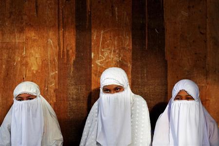 Muslim students of a boarding school listen to their teacher reading Koran in Banda Aceh December 12, 2012. REUTERS/Damir Sagolj