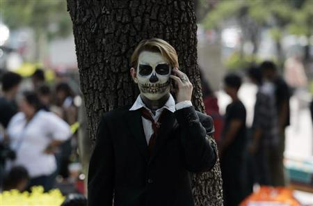 A fine arts student wears make-up as he talks on the phone during the Catrina's parade in Guadalajara October 26, 2012. REUTERS/Alejandro Acosta